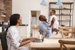 当父亲拿着小女儿,母亲从家工作 库存图片