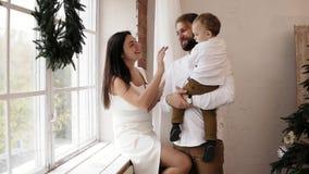 当白色礼服的可爱的母亲坐时,年轻父亲拿着他的男婴,支持窗口 股票录像