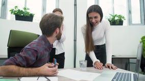 当看膝上型计算机屏幕时,愉快的办公室工作者高兴在生长率 获得的同事乐趣一起 妇女 股票录像