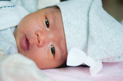 当睡觉和使用在床上/接近在逗人喜爱新出生看照相机时,聚焦在有灰色帽子的亚裔女婴 库存照片