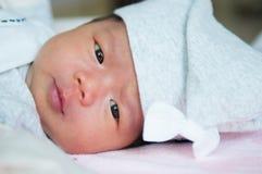 当睡觉和使用在床上/接近在逗人喜爱新出生看照相机时,聚焦在有灰色帽子的亚裔女婴 图库摄影
