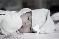 当睡觉和使用在床上/接近在逗人喜爱新出生看照相机时,聚焦在有灰色帽子的亚裔女婴 免版税库存照片
