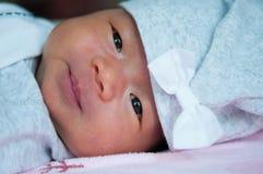 当睡觉和使用在床上/接近在逗人喜爱新出生看照相机时,聚焦在有灰色帽子的亚裔女婴 免版税库存图片