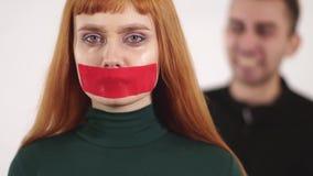 当积极的恼怒的人是叫喊和叫喊对女性时,年轻女人画象有录音的嘴的是沈默的 影视素材
