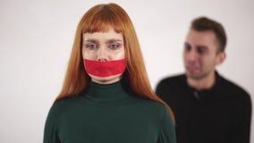 当积极的恼怒的人是叫喊和叫喊对女性时,年轻女人画象有录音的嘴的是沈默的 股票录像