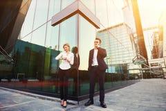 当站立与外面时,伙伴男性企业家叫与手机 免版税库存图片