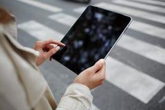 当等待在街道上时的汽车女实业家特写镜头在她的触摸板读电子邮件 免版税库存照片