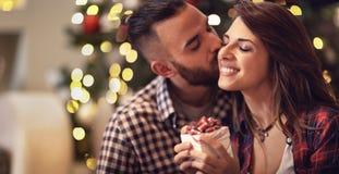 当给她的圣诞节礼物时,人亲吻妇女 库存照片