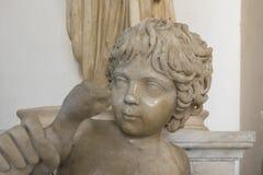 当赫拉克勒斯chokin被刻画的年轻男孩雕象的片段 库存图片