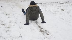 当走在公园在冬天滑倒了并且失去了他的平衡时,年轻人时髦地打扮了人 免版税库存照片