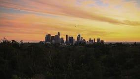 当软式小型飞艇飞行上面街市,太阳在洛杉矶地平线落 股票录像
