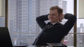 当达到目标时,成功的商人在办公室在头后去除手 影视素材