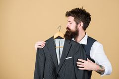 当邀请时正式说 礼服精品店的有胡子的人 选择在衣橱的行家正装夹克 库存图片