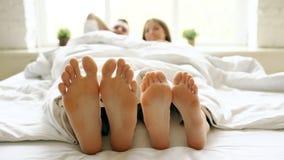 当醒在床上在早晨时,年轻美好和爱恋的夫妇特写镜头演奏并且跳舞他们的脚在毯子下 免版税库存图片