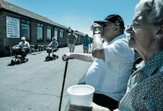 当领抚恤金者在动力化的推车,巡航年长夫妇啜饮茶 图库摄影
