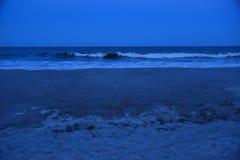 当黑暗降临,在接踵而来的波浪的白色盖帽发光 免版税图库摄影