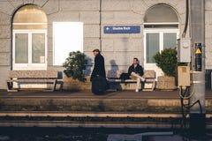 当年轻人坐长凳在驻地平台附近时,老人留下火车站 免版税库存图片