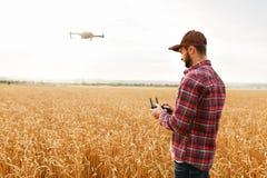 当直升机在背景时,飞行农夫拿着遥远的控制器用他的手 寄生虫在农艺师后盘旋 免版税库存图片
