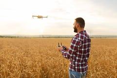 当直升机在背景时,飞行农夫拿着遥远的控制器用他的手 寄生虫在农艺师后盘旋 免版税库存照片