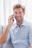 当他有一次电话交谈时,供以人员微笑 免版税库存照片