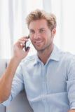 当他有一次电话交谈时,供以人员微笑 库存照片