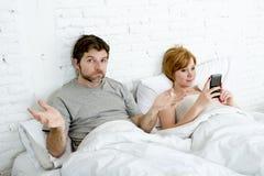 当他的互联网上瘾者妻子使用手机时,在床丈夫的夫妇挫败了翻倒和不满意 免版税库存照片