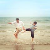当他的儿子设法得到它时,生在踢球的海滩 免版税库存照片