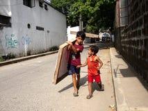 当他的更加年轻的伴侣看在并且与他,谈话一个年轻男孩运载一块木头 免版税库存图片