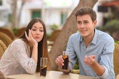 当他讲话时,男人和妇女约会,但是她烦人 免版税库存图片