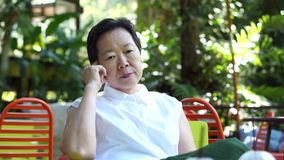 录影亚洲资深妇女认为和忧虑在绿色豪华的自然背景中 影视素材