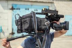 录影生产、摄影师或者操作员用专业电影摄影机设备在户外工作,电视广播 免版税图库摄影