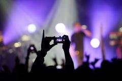 给录影记录打电话一个摇滚乐队的表现在音乐会的 库存照片