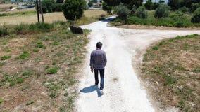 录影走沿乡下公路的从上面一个人佩带的牛仔裤、格子衬衫和太阳镜人 Dron追求 股票录像