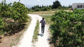 录影跑沿乡下公路的从上面一个人佩带的牛仔裤、格子衬衫和太阳镜人 Dron追求 影视素材