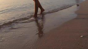 录影镜头,在海滩沙波海的妇女腿日出的 股票录像