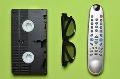录象带,电视遥控, 3d在绿色淡色背景的玻璃 娱乐90s 顶视图 库存图片