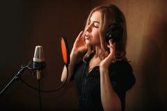 录音歌的女歌手在音乐演播室 免版税库存图片