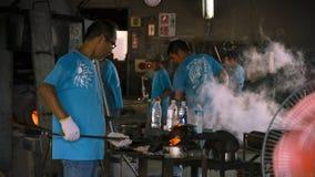 形成一块热的玻璃的未认出的人在Ryukyu玻璃村庄 库存照片