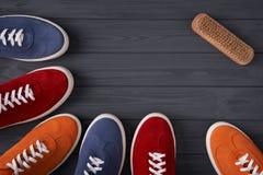 形成与拷贝空间的五颜六色的绒面革运动鞋一个框架,在灰色木板条 免版税库存照片