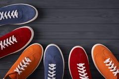 形成与拷贝空间的五颜六色的绒面革运动鞋一个框架,在灰色木板条 库存图片