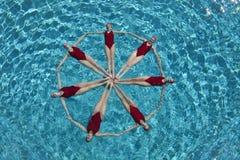 形成圈子的同步的游泳者 免版税库存图片