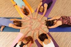 形成圈子/Vinyasa流程瑜伽的妇女的手 免版税库存照片