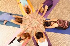 形成圈子/Vinyasa流程瑜伽的妇女的手 图库摄影