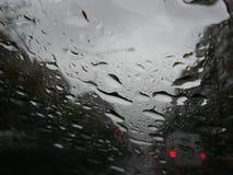 形成在挡风玻璃的雨珠条纹 免版税库存照片