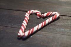 形成在黑暗的木板条背景的红色和白色棒棒糖心脏  关闭 婴孩圣诞节克劳斯帽子演奏s圣诞老人的母亲照片一起佩带 图库摄影