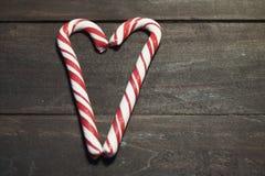 形成在黑暗的木板条背景的红色和白色棒棒糖心脏  关闭 婴孩圣诞节克劳斯帽子演奏s圣诞老人的母亲照片一起佩带 库存照片