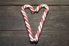 形成在黑暗的木板条背景的红色和白色棒棒糖心脏  关闭 婴孩圣诞节克劳斯帽子演奏s圣诞老人的母亲照片一起佩带 免版税库存图片