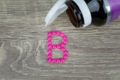 形成形状的桃红色药片对在木背景的B字母表 免版税图库摄影