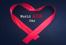 形成心脏形状的红色丝带与世界艾滋病日 图库摄影