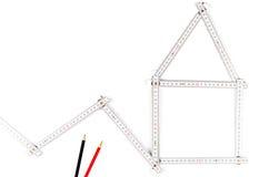 形成房子,在白色的两支画的铅笔的白色米工具 免版税库存图片